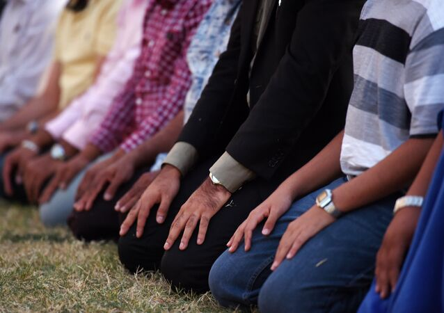 Muslim men kneel to pray