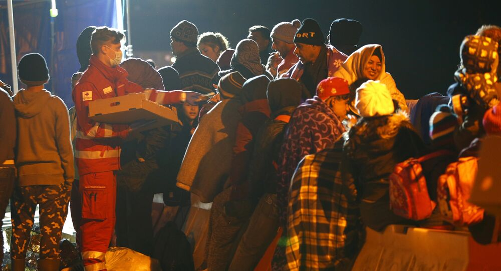 Migrants wait on the bridge at the Austrian-German border between Braunau and Simbach at lake Inn near Passau, Germany, October 27, 2015