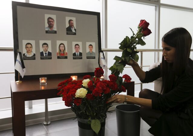 A woman places flowers in front of the portraits of crew members of the crashed Airbus A321 plane, operated by Russian airline Kogalymavia, in the company's office in Moscow, Russia November 2, 2015