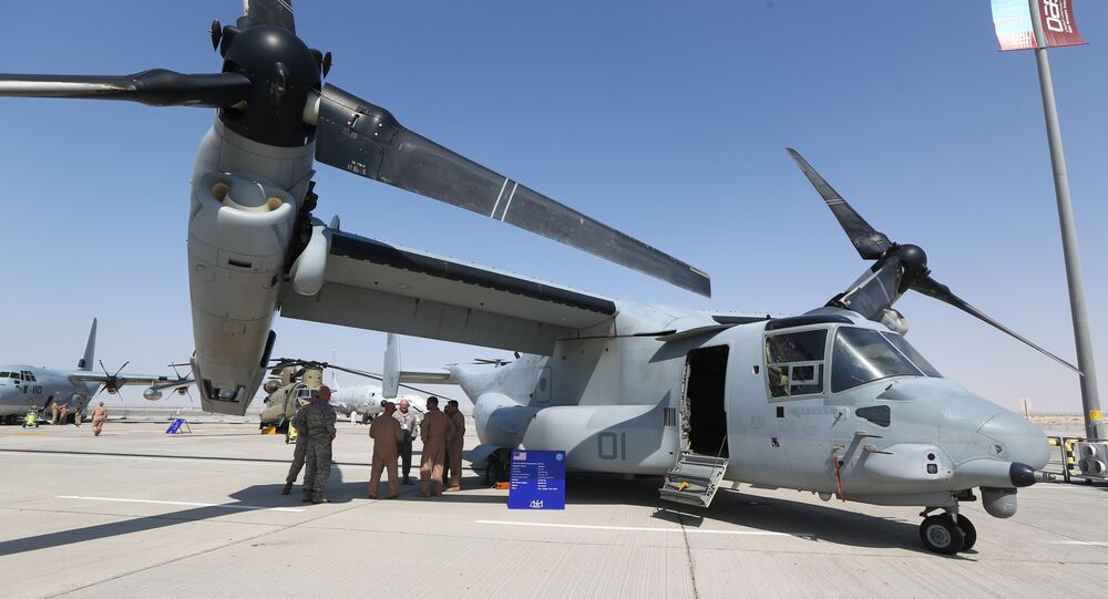 US soldiers stand in the shade of the wing of a Bell Boeing V-22 Osprey, a US multi-mission, tiltrotor military aircraft, displayed at the Dubai Airshow on November 8, 2015