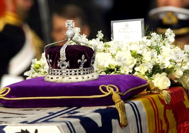 The Koh-i-noor, or mountain of light, diamond, set in the Maltese Cross at the front of the crown made for Britain's late Queen Mother Elizabeth, is seen on her coffin, along with her personal standard, a wreath and a note from her daughter, Queen Elizabeth II, as it is drawn to London's Westminster Hall in this April 5, 2002 file photo.