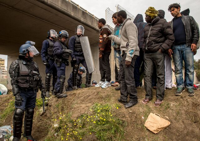 French police officers proceed with operations during the eviction of migrants from a camp site in Calais.