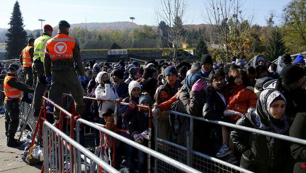 Austrian army soldiers observe migrants as they wait to cross the border from the village of Sentilj, Slovenia into Spielfeld in Austria, November 2, 2015 - Sputnik International