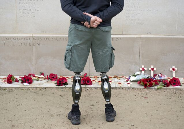 A member of the armed forces with prosthetic legs pays his respects at the Armed Forces Memorial in the National Memorial Arboretum on Armistice Day near Lichfield, Staffordshire, central England, on November 11, 2014.