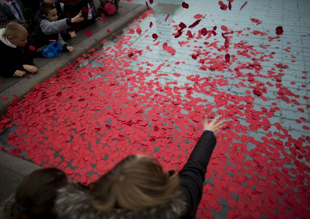 School pupils throw poppies into a fountain after observing a two minute silence to mark Armistice Day, in Trafalgar Square, London, Wednesday, Nov. 11, 2015.