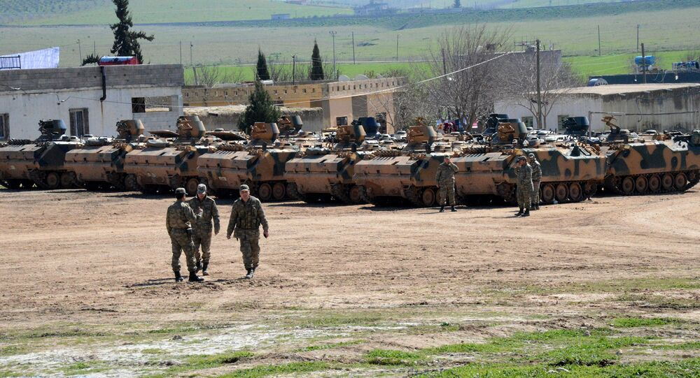 Turkish Army vehicles and tanks wait near the Syrian border in Suruc
