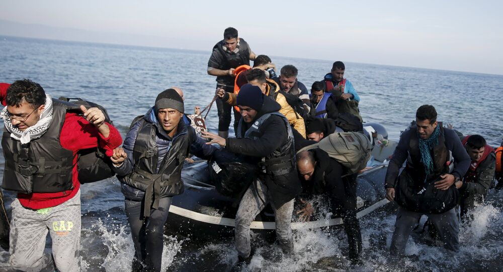 File Photo: Refugees and migrants jump off an inflatable raft as they arrive on the Greek island of Lesbos, November 11, 2015