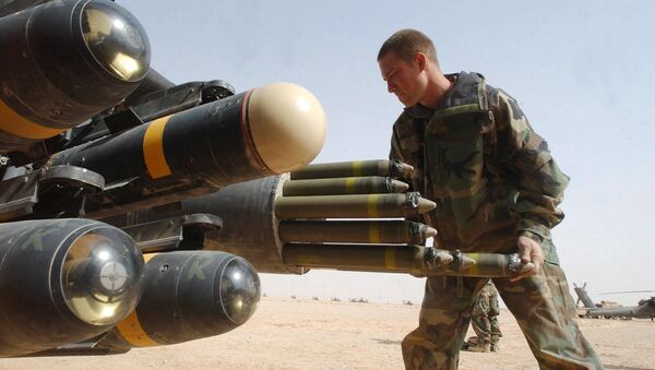 US Army armament crew specialist Michael Mayo, from Florida, loads the rocket pod of an an Apache AH-64D attack helicopter also armed with Hellfire missiles at left - Sputnik International