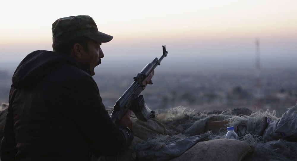 A Kurdish fighter, known as a peshmerga, yawns as he stands guard on the frontline in Sinjar, Iraq, Friday, Nov. 13, 2015.