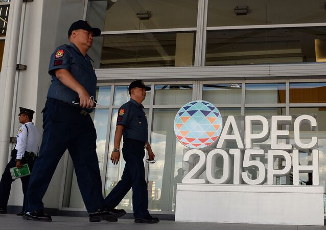 Philippine policemen walk past an Asia Pacific Economic Cooperation (APEC) summit logo in front of the media centre in Manila