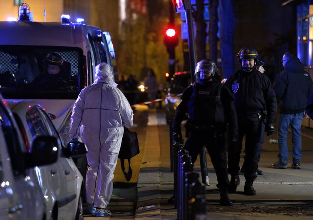 An investigating police officer, left, arrives outside the Stade de France stadium after an international friendly soccer match France against Germany, in Saint Denis, outside Paris, Friday Nov. 13, 2015.