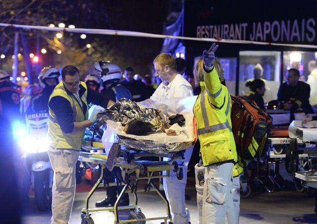 Rescuers evacuate an injured person near the Bataclan concert hall in central Paris, early on November 14, 2015