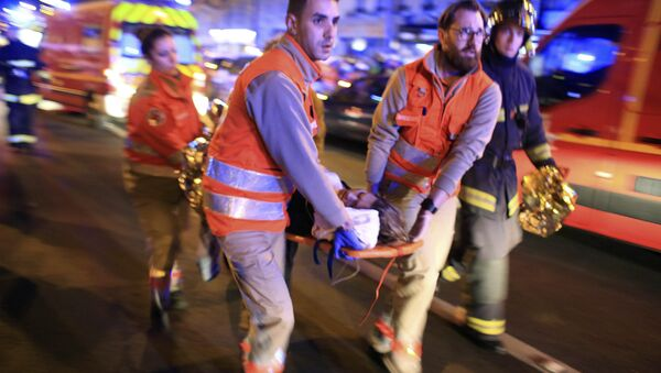 A woman is being evacuated from the Bataclan theater after a shooting in Paris, Friday Nov. 13, 2015 - Sputnik International