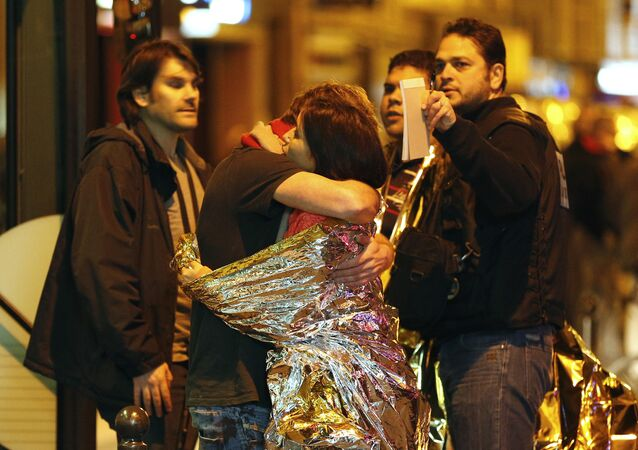 People hug each other before being evacuated by bus, near the Bataclan concert hall in central Paris, on November 14, 2015