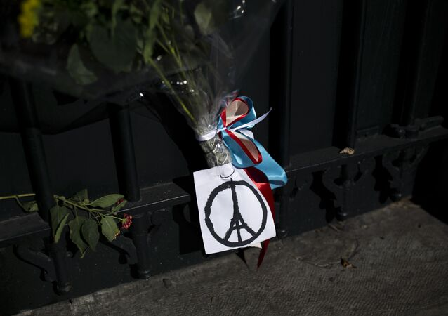 Flowers and a peace sign in the shape of the Parisian landmark the Eiffel Tower, are seem outside French Embassy in Greece on November 14, 2015, a day after deadly attacks in Paris