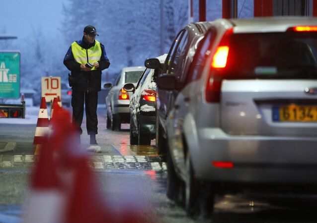 Swiss border guard hands out leaflets informing drivers crossing into Switzerland at Bardonnex