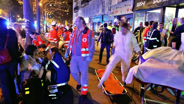 People rest on a bench after being evacuated from the Bataclan theater after a shooting in Paris, Saturday, Nov. 14, 2015 - Sputnik International