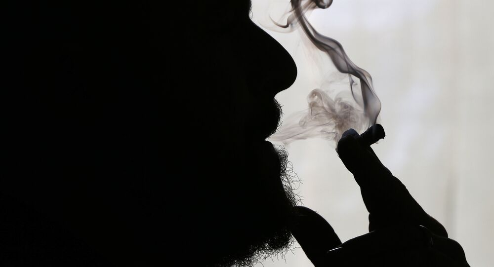 Former US Marine Sgt. Ryan Begin smokes medical marijuana at his home in Belfast, Maine. Begin had his right elbow blown off by a roadside bomb in 2004 and suffers from post-traumatic stress disorder.