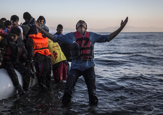 A young man gestures after disembarking from a dinghy at a beach on the Greek island of Lesbos after crossing the Aegean sea from the Turkish coast, Saturday, Nov. 14, 2015