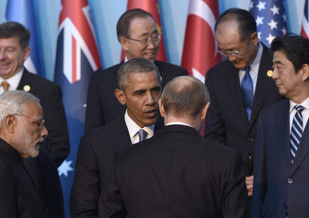 President Barack Obama, center, talks with Russia's President Vladimir Putin, center right, as they arrive for a group photo with other leaders for the G-20 Summit in Antalya, Turkey, Sunday, Nov. 15, 2015