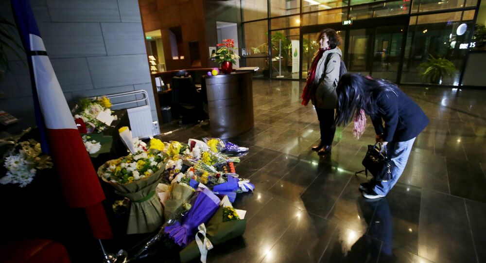 A woman bows after laying flowers to mourn the victims of the attacks on November 13 in Paris, at the French Embassy in Beijing, China, November 15, 2015