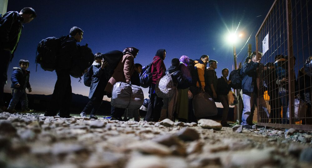 Migrants and refugees enter a registration camp after crossing the Greek-Macedonian border near Gevgelija on November 13, 2015