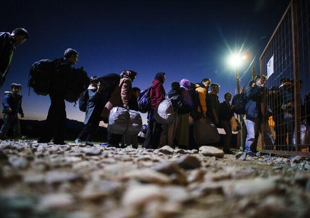 Migrants and refugees enter a registration camp after crossing the Greek-Macedonian border near Gevgelija on November 13, 2015