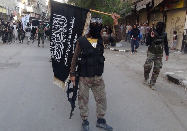 Islamic fighters from the al-Qaida group in the Levant, Al-Nusra Front, wave their movement's flag as they parade at the Yarmuk Palestinian refugee camp, south of Damascus, to denounce Israel's military offensive on the Gaza Strip, on July 28, 2014