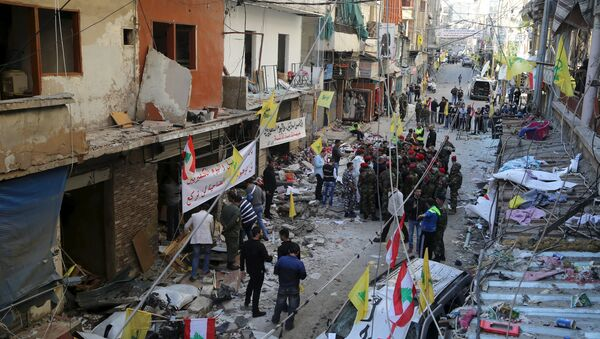 Lebanese army soldiers and security forces gather as Lebanese and Hezbollah flags are erected at the site of the two explosions that occured on Thursday in the southern suburbs of the Lebanese capital Beirut, November 13, 2015 - Sputnik International