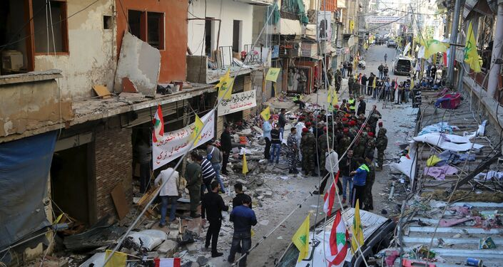 Lebanese army soldiers and security forces gather as Lebanese and Hezbollah flags are erected at the site of the two explosions that occured on Thursday in the southern suburbs of the Lebanese capital Beirut, November 13, 2015