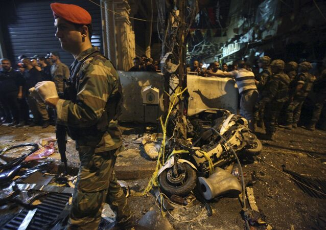 Residents and Lebanese army members inspect a damaged area caused by two explosions in Beirut's southern suburbs, Lebanon November 12, 2015