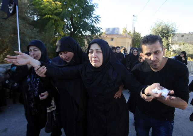 Zahraa al-Athath, second right, wife of Hezbollah member Adel Termos, who was killed in Thursday's twin suicide bombings, mourns during his funeral procession in the southern Lebanese village of Tallousa, Lebanon, Friday, Nov. 13, 2015