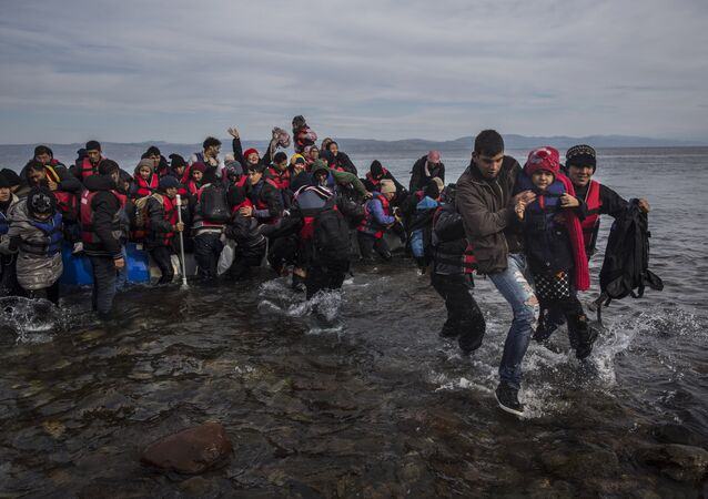 Migrants and refugees disembark safely from a dinghy at a beach on the Greek island of Lesbos after crossing the Aegean sea from the Turkish coast, Monday, Nov. 16, 2015
