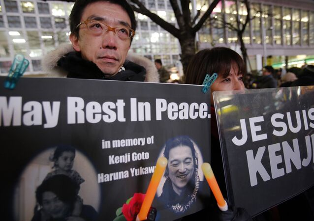 People gather to mourn two Japanese hostages, Kenji Goto and Haruna Yukawa, who were killed by the Islamic State group, in Tokyo, Sunday, Feb. 8, 2015