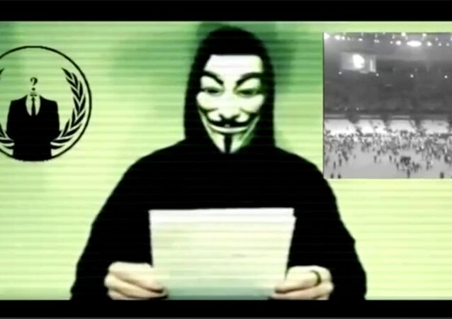 Still image from a video shows a man wearing a mask associated with Anonymous making a statement