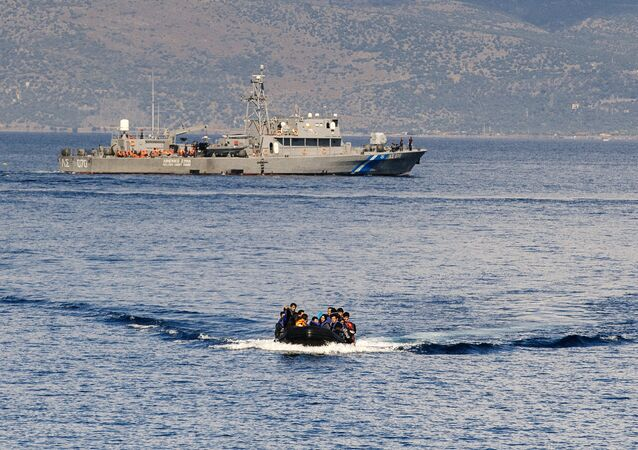 A Greek coast guard ship is seen behind a rubber boat with refugees and migrants near the Greek island of Lesbos after crossing the Aegean Sea from Turkey on October 13, 2015