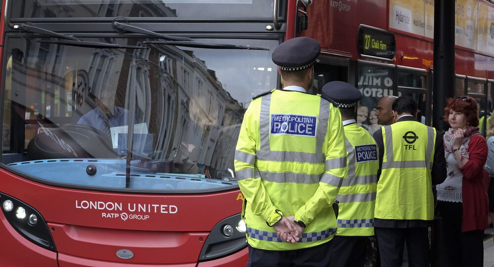 Police officers stand guard at a bus stop outside Paddington Station in London.