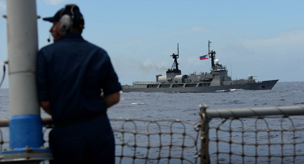 US Navy personnel looks at Philippine Navy vessel BRP Ramon Alcaraz during the bilateral maritime exercise between the Philippine Navy and US Navy dubbed Cooperation Afloat Readiness and Training (CARAT 2014) aboard the USS John S. McCain in the South China Sea near waters claimed by Beijing on June 28, 2014