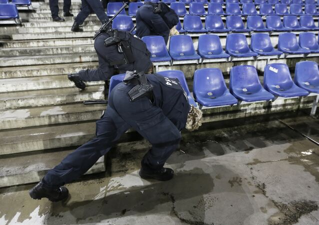 German police officers search between the seats of the stadium prior to an international friendly soccer match between Germany and the Netherlands in Hannover, Germany, Tuesday, Nov. 17, 2015.