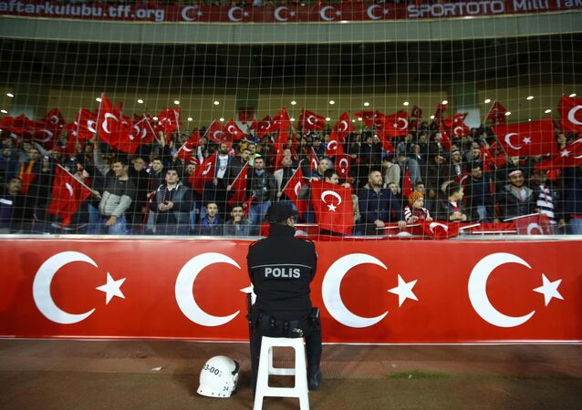 A policeman stands guard in front of supporters of Turkey during their international friendly soccer match against Greece at Basaksehir Fatih Terim stadium in Istanbul, Turkey November 17, 2015