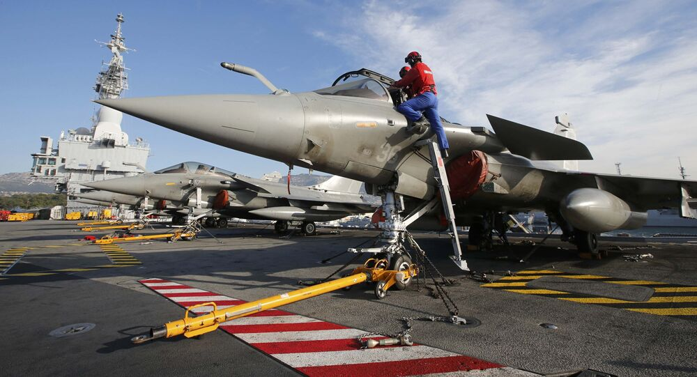 Flight deck crew work on Rafale fighter jets aboard the French nuclear-powered aircraft carrier Charles de Gaulle before its departure from the naval base of Toulon, France, November 18, 2015
