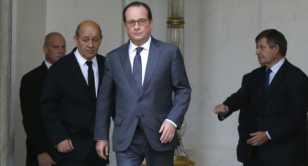 French President Francois Hollande (C) and French Defence minister Jean-Yves Le Drian (L) leave the weekly cabinet meeting at the Elysee Palace in Paris