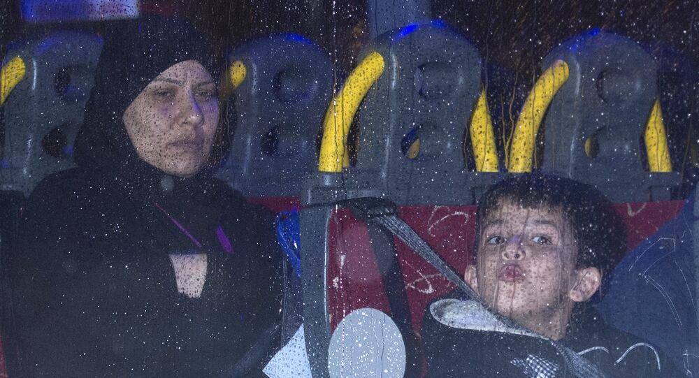 Syrian refugees are driven away after landing at Glasgow airport, Scotland on November 17, 2015.