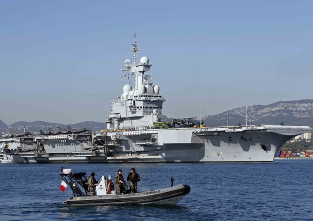 French army soldiers secure the area around the nuclear-powered aircraft carrier Charles de Gaulle as it leaves the naval base of Toulon, France