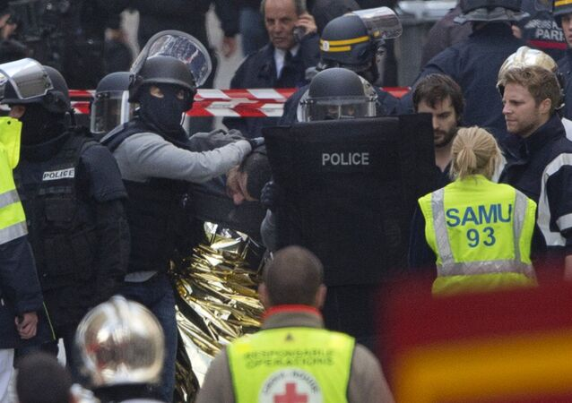Hooded police officers detain a man in Saint-Denis, near Paris, Wednesday, Nov. 18, 2015. A woman wearing an explosive suicide vest blew herself up Wednesday as heavily armed police tried to storm a suburban Paris apartment where the suspected mastermind of last week's attacks was believed to be holed up, police said.