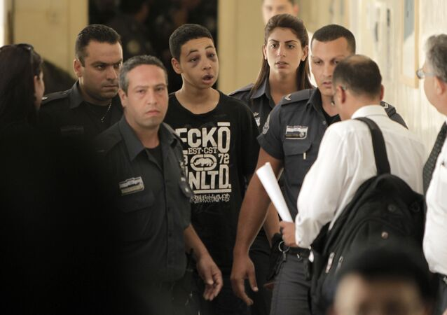 Tariq Abu Khder (C), a Palestinian-US teenager who was allegedly beaten during police custody, arrives for a hearing at Jerusalem Magistrates Court on July 6, 2014.