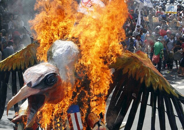 Protesters burn an effigy during a rally near the venue of the Asia-Pacific Economic Cooperation (APEC) summit, in Manila November 19, 2015