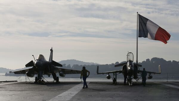 Flight deck crew work around a Rafale (L) and a Super Etendard fighter jets as a French flag flies aboard the French nuclear-powered aircraft carrier Charles de Gaulle before its departure from the naval base of Toulon, France, November 18, 2015 - Sputnik International