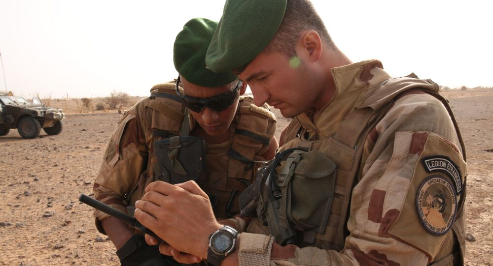 In this photo taken Sunday, June 21, 2015, French soldiers look at their sat phone as they are on patrol in the desert south of the village of Deliman, Mali.