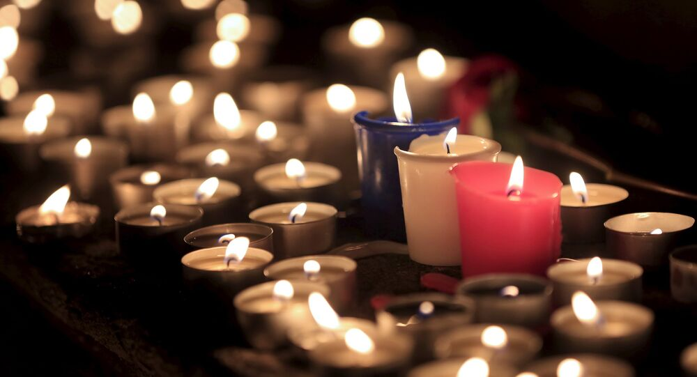 Candles are seen at a memorial tribute to the victims of attacks in Paris